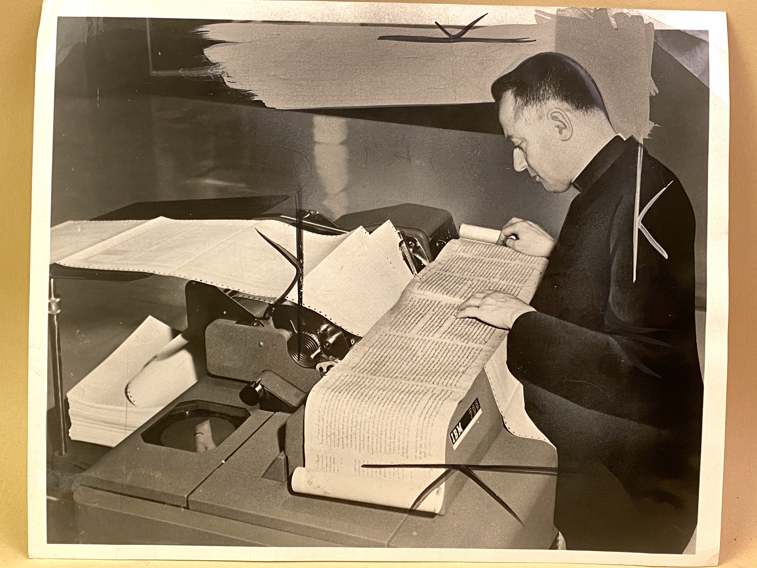 This press photo of Robert Busa comparing the text of the Dead Sea Scrolls with print-outs from the IBM 705 shows crop marks and white-outs from the publication process.