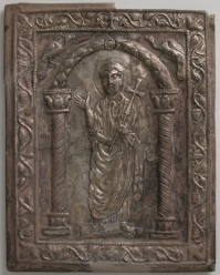 "Byzantine repousse silver bookbinding cover depicting St. Peter, holding a cross and gesturing as if preaching. At his waste are the keys to the kingdom of heaven given to him by Christ (Matthew 16;19). ""The arch flanked by peacocks under which Peter stands is considered a representation of paradise in early Christian art."