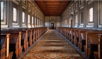 """The Reading Room, which unlike the Vestibule develops horizontally, hosts two series of wooden benches, the so-called plutei, which functioned as lecterns as well as book-shelves. They were designed by Michelangelo and, according to Giorgio Vasari, work of Giovan Battista del Cinque and Ciapino."""