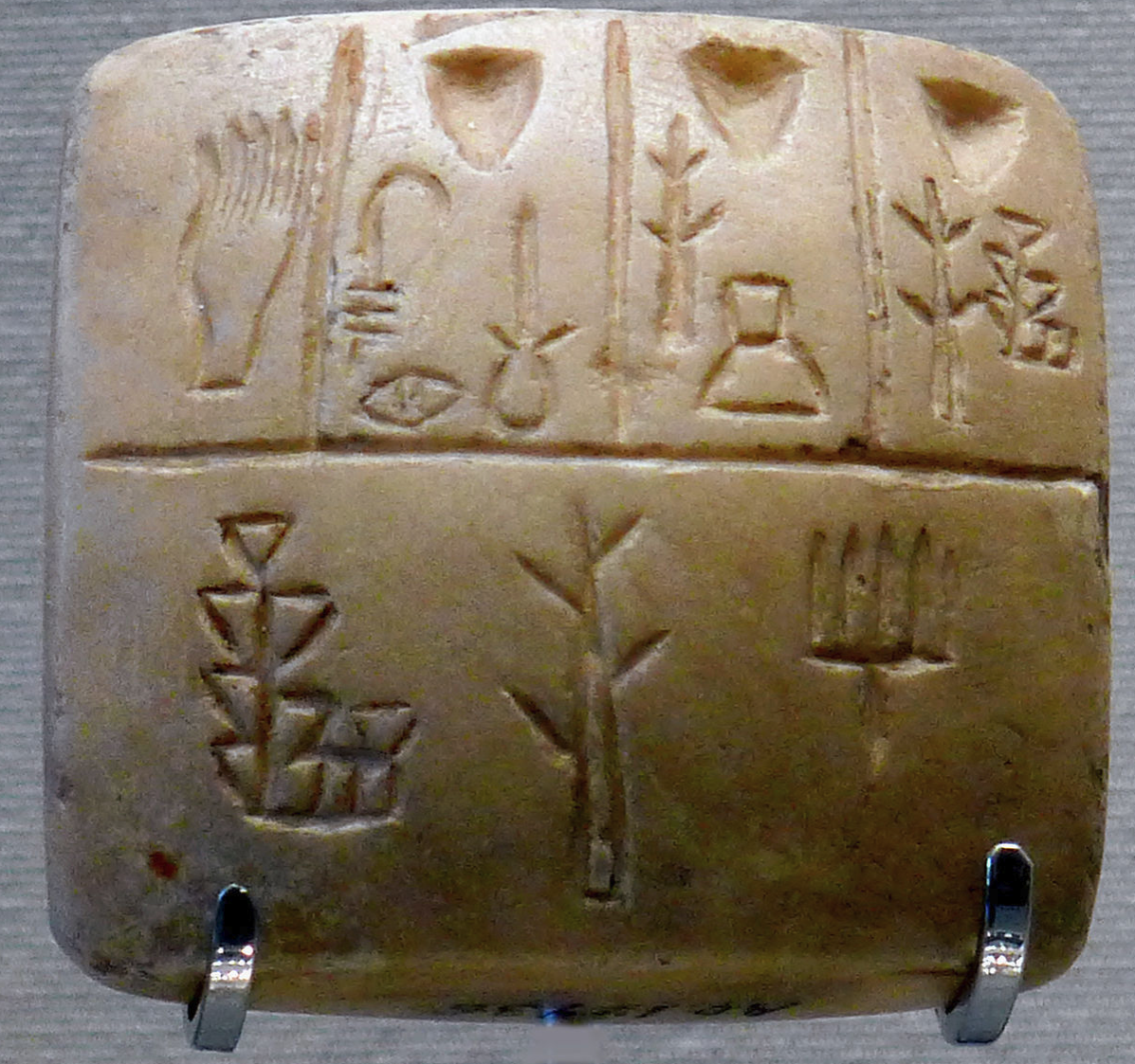 Tablet with proto-cuneiform pictographic characters (end of 4th millennium BC), Uruk III. This is thought to be a list of slaves names, the hand in the upper left corner representing the owner.[25]