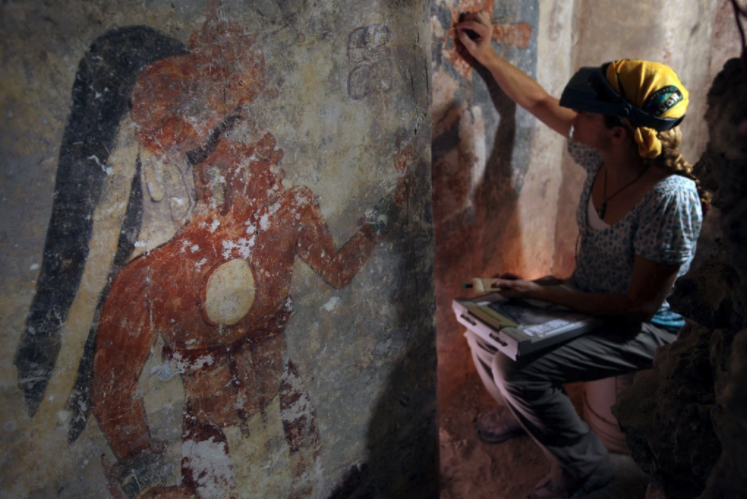 Angelyn Bass cleans and stabilizes the surface of a wall that shows the figure of a man who may have been the town scribe.Credit...Tyrone Turner/National Geographic.