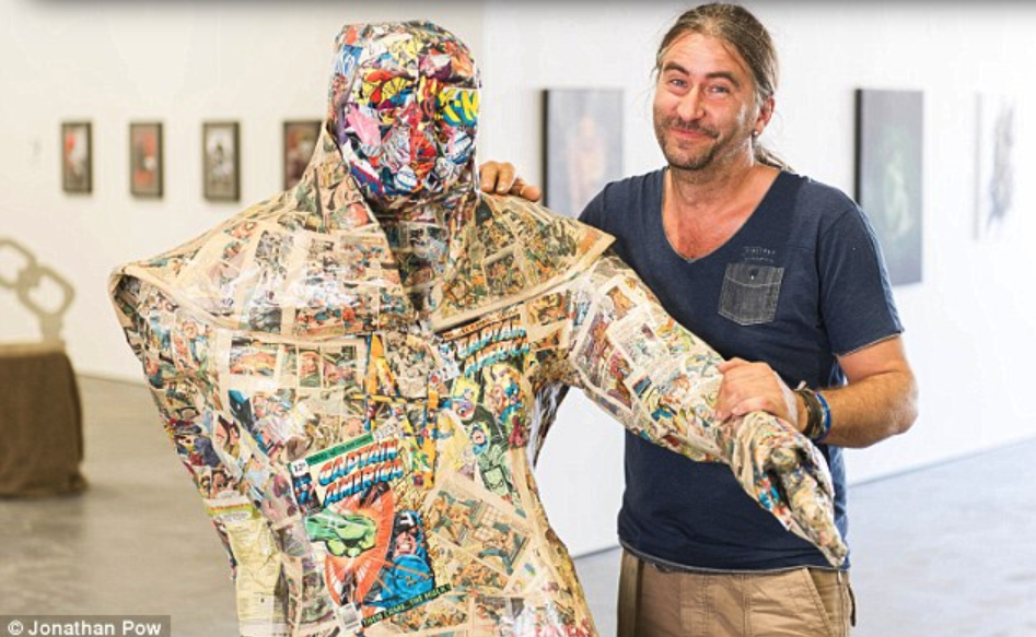 """Oops: Andrew Vickers pictured with his sculpture called Paperboy which he created using £20,000 of comics."""