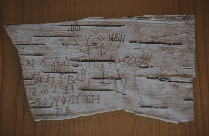 Message and drawing left by a boy on a birch scroll in Old Novgorod language, a precursor to Russian. The scroll was dug from the preservative mud of Veliky Novgorod. (Sergey Ponomarev for The New York Times).