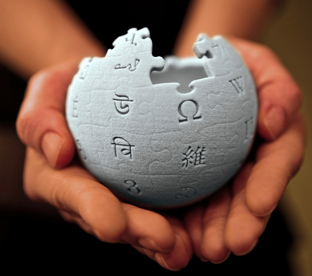 3D model of Wikipedia log held in the palm of two hands