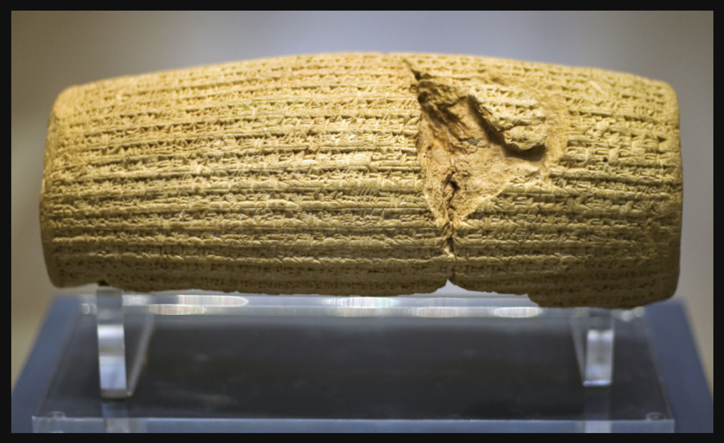 Front view of a barrel-shaped clay cylinder resting on a stand. The cylinder is covered with lines of cuneiform text. British Museum.