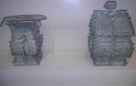 "Left item: A Chinese bronze ""fang zun"" ritual wine container, from the Western Zhou Dynasty, dated c. 1000 BC, excavated in modern-day Luoyang. The written inscription cast in bronze on the v"