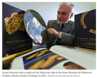 Scientist with replica of the Nebra Sky Disk